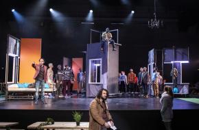 Het toneel oogt als een dorpsgemeenschap bevolkt door tientallen mensen, professionele acteurs, musici en dansers